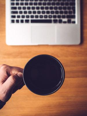 Mężczyzna siedzi przy biurku i pije kawę