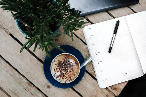 Filiżanka z kawą leżą na stole obok kalendarza